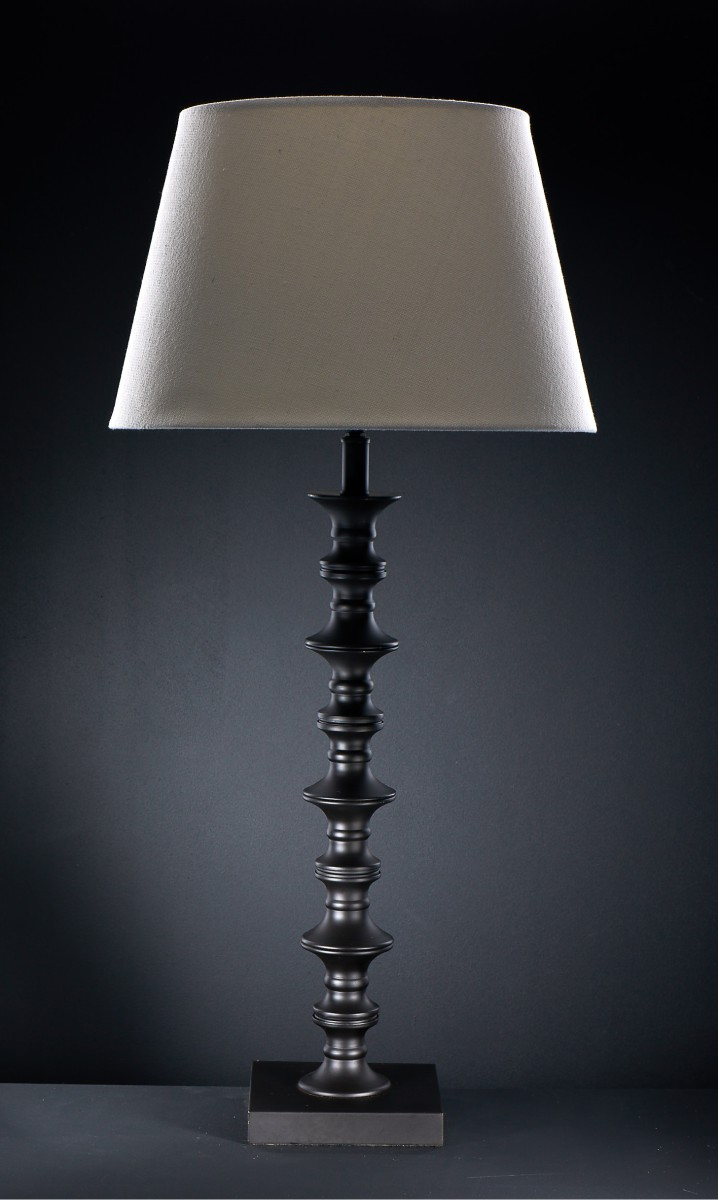 Tall black wood lamp and beige shade for sales brochure